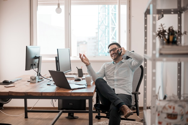 Portret van de glimlachende mens die op mobiele telefoon spreekt, die bij bureau zit.