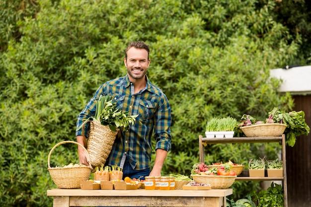 Portret van de glimlachende mens die organische groenten verkoopt