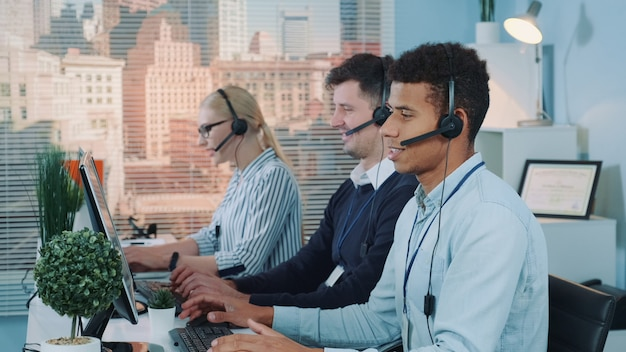 Portret van de glimlachende mens die van het gemengd ras vraag in bezig call centre nemen