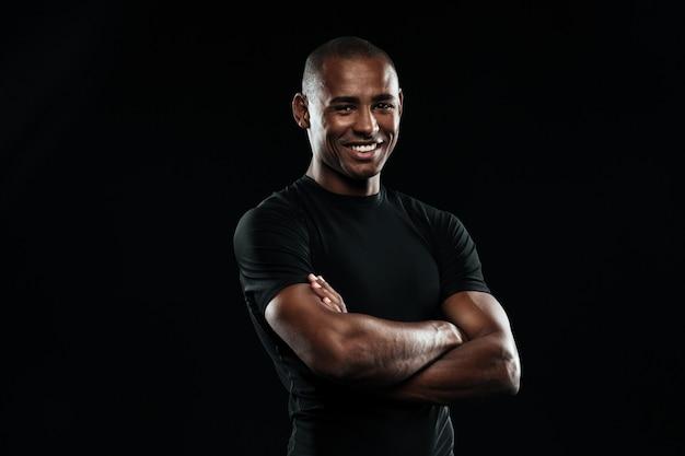 Portret van de glimlachende mens van afro amerikaanse sporten met wapens het gevouwen bekijken camera