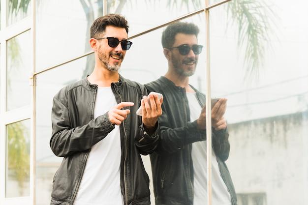 Portret van de glimlachende modieuze mens die zonnebril draagt die mobiele telefoon met behulp van