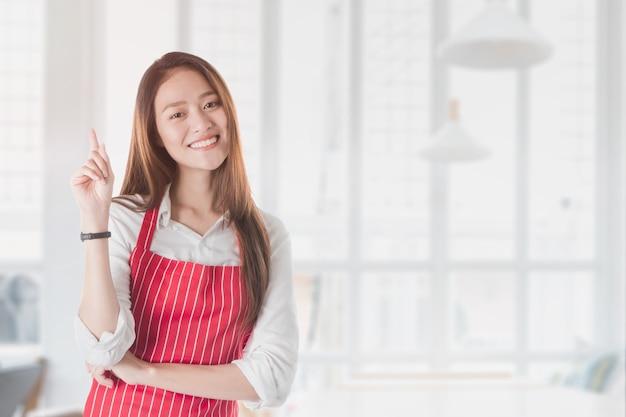 Portret van de glimlachende mooie aziatische schort van de vrouwenslijtage en hand het richten