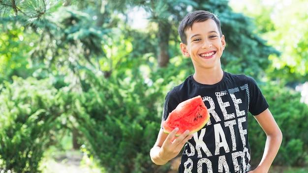 Portret van de glimlachende plak van de jongensholding van watermeloen in openlucht