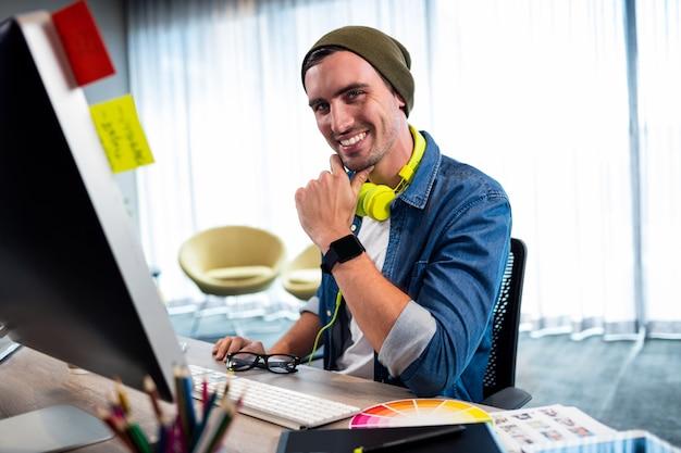 Portret van de glimlachende toevallige mens die bij computerbureau werkt