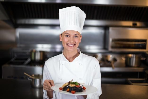 Portret van de glimlachende vrouwelijke plaat van de chef-kokholding
