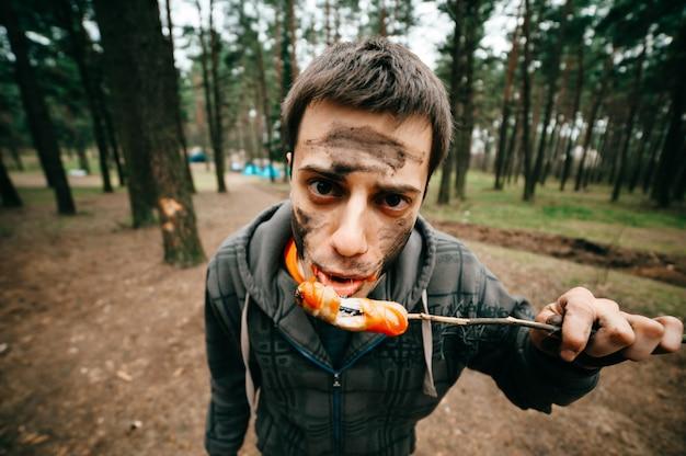 Portret van de grappige mens met vuil gezicht die gebraden worst in het bos wating