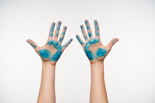 Portret van de handen van een blanke vrouw met blauwe verf erop met de handpalmen en het apart houden van alle vingers, geïsoleerd op wit