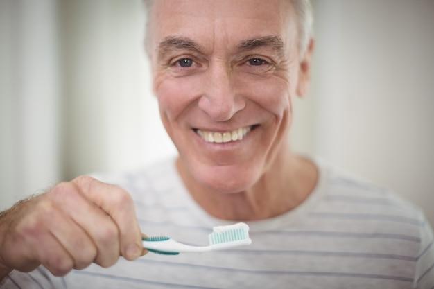 Portret van de hogere mens die zijn tanden in badkamers borstelt