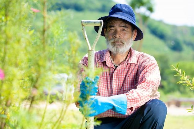 Portret van de hogere mens met het tuinieren hulpmiddelen die in openlucht in de tuin werken.