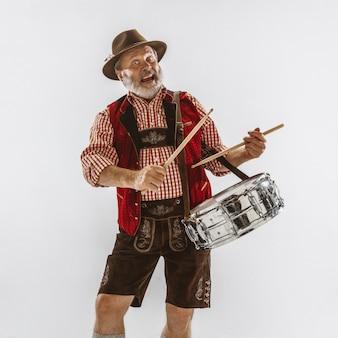 Portret van de hogere mens oktoberfest in hoed, die de traditionele beierse kleren draagt. mannetje dat van gemiddelde lengte bij studio op witte achtergrond is ontsproten. de viering, vakantie, festivalconcept. drummen.