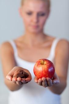 Portret van de holdingschocolade van de awoman en appelfocus op appel