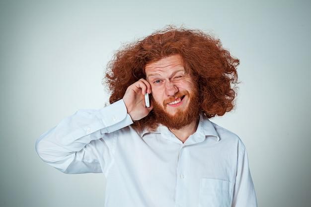 Portret van de in verwarring gebrachte mens die op de telefoon een grijze achtergrond spreekt