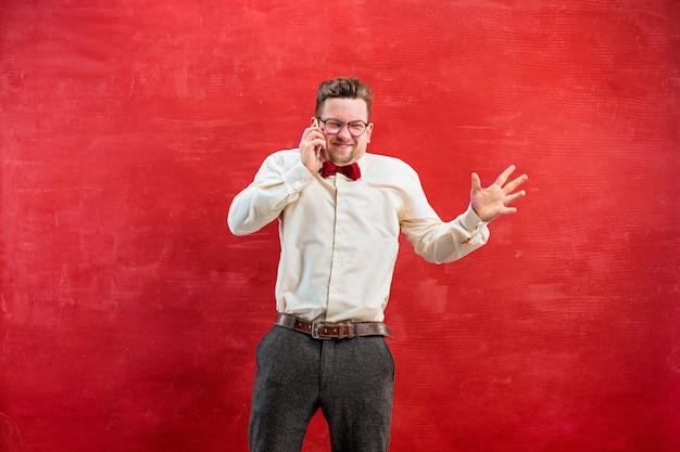 Portret van de in verwarring gebrachte mens die telefonisch een rode achtergrond spreekt