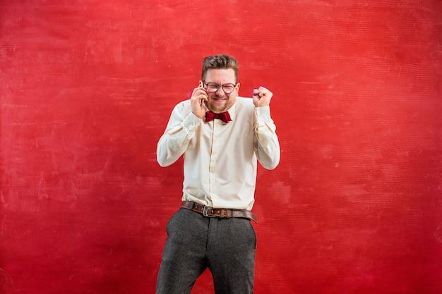 Portret van de in verwarring gebrachte mens die telefonisch op rood spreekt