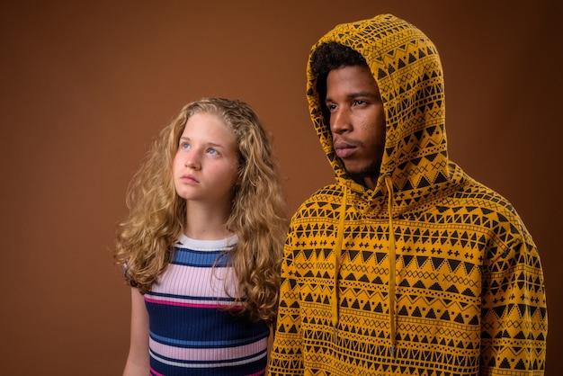 Portret van de jonge afrikaanse man en het kaukasische tienermeisje denken
