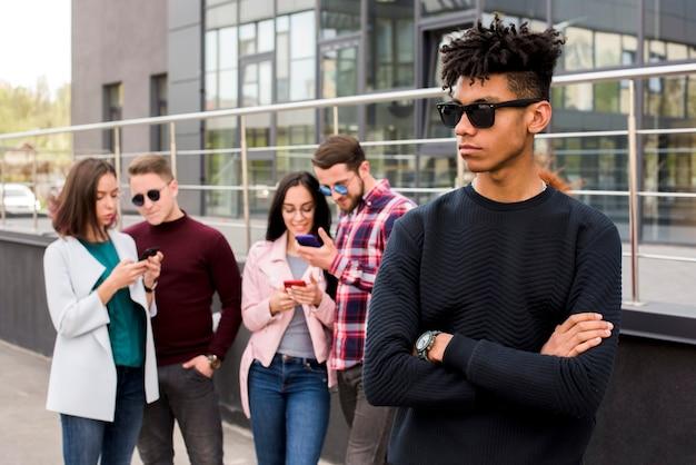 Portret van de jonge afrikaanse mens die terwijl zijn vrienden bezig in mobiele telefoon stelt
