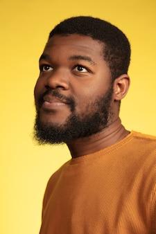 Portret van de jonge afro-amerikaanse man geïsoleerd op gele studio achtergrond, gezichtsuitdrukking.