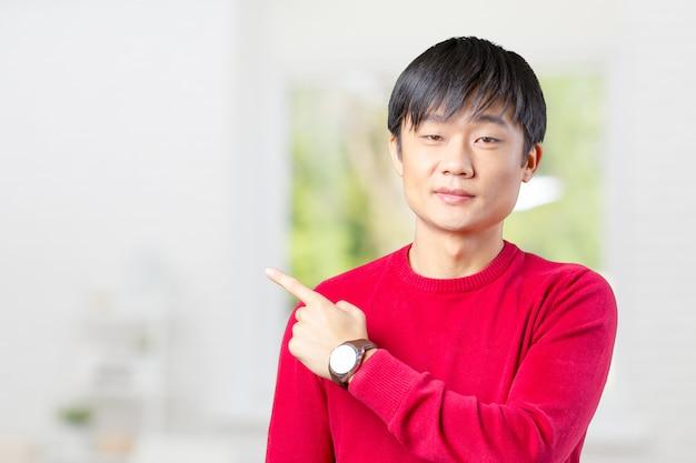 Portret van de jonge aziatische mens die met zijn vinger richt