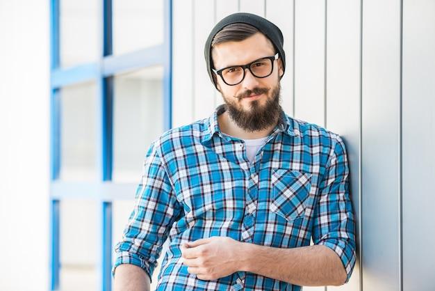 Portret van de jonge bebaarde man in hoed en bril buiten.