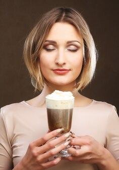 Portret van de jonge blonde kop van de koffie latte van de vrouwenholding