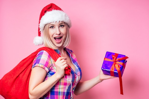 Portret van de jonge blonde verbaasde vrouw van beautyful met de gift van de kerstmisdoos op rode achtergrond