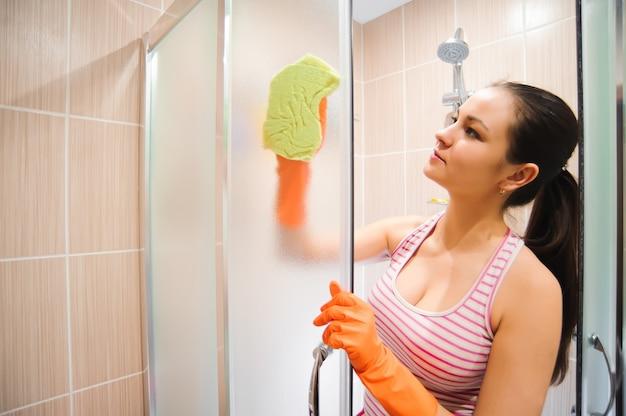 Portret van de jonge deur van de vrouwen schoonmakende douche.