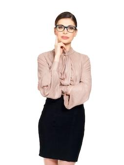 Portret van de jonge ernstige vrouw in glazen en beige overhemd met zwarte rok- die op witte achtergrond wordt geïsoleerd