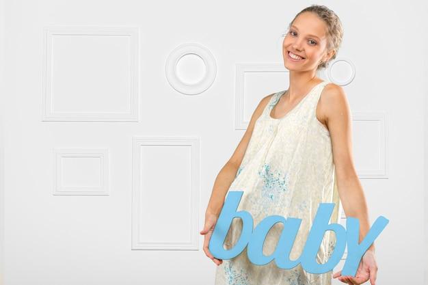 Portret van de jonge gelukkige glimlachende zwangere vrouw