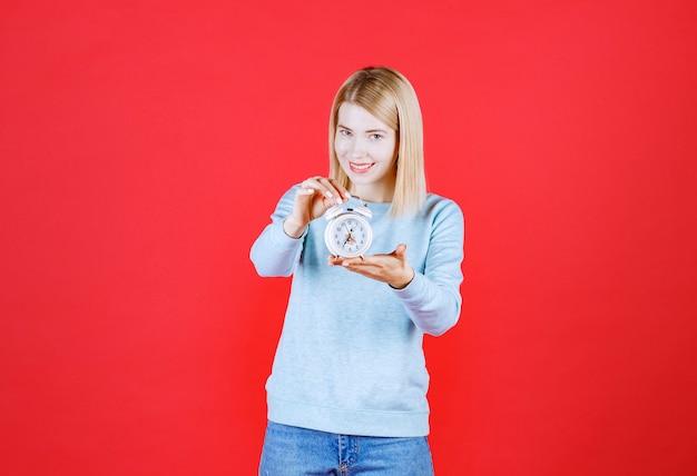 Portret van de jonge klok van de vrouwenholding en wil iemand op een rode muur geven