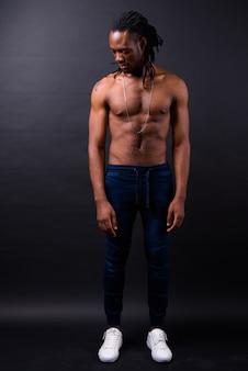 Portret van de jonge knappe afrikaanse man met dreadlocks shirtless op zwart