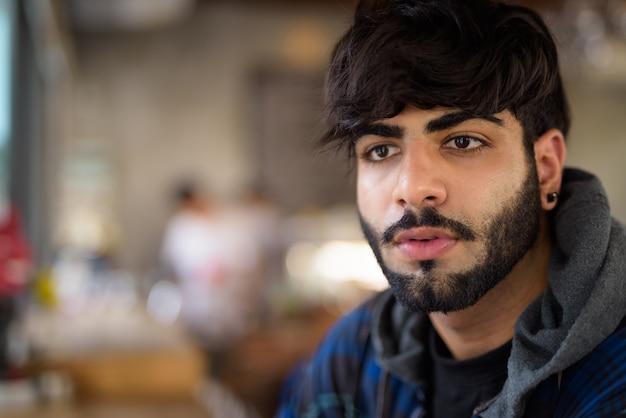 Portret van de jonge knappe bebaarde indiase hipster man ontspannen in de coffeeshop