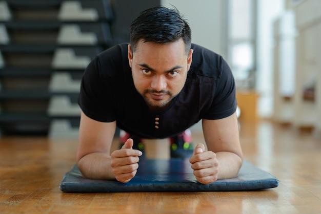 Portret van de jonge knappe bebaarde indiase man trainen in de sportschool