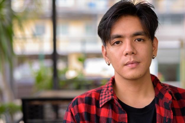 Portret van de jonge knappe filipijnse hipster man ontspannen in de coffeeshop