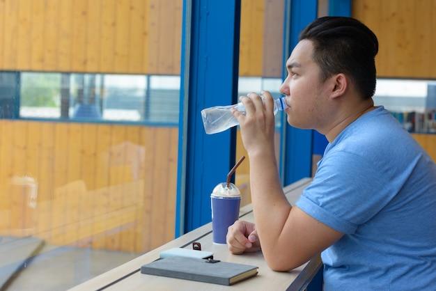 Portret van de jonge knappe filipijnse man met overgewicht ontspannen in de coffeeshop Premium Foto
