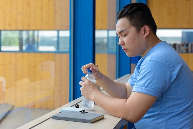 Portret van de jonge knappe filipijnse man met overgewicht ontspannen in de coffeeshop