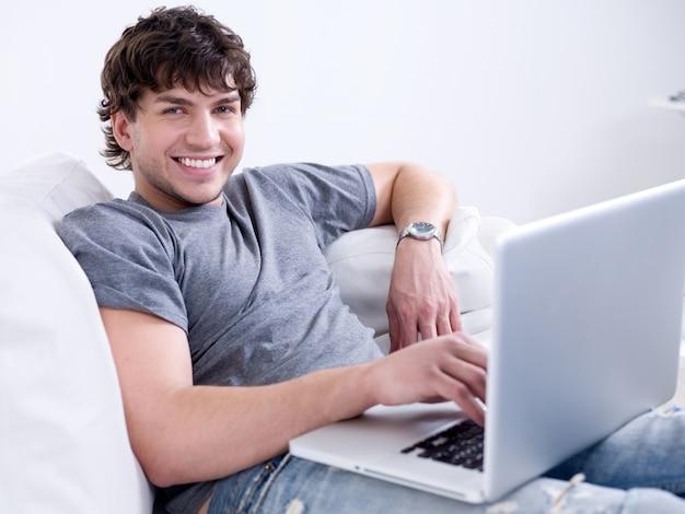 Portret van de jonge knappe glimlachende mens die op laptop thuis werkt