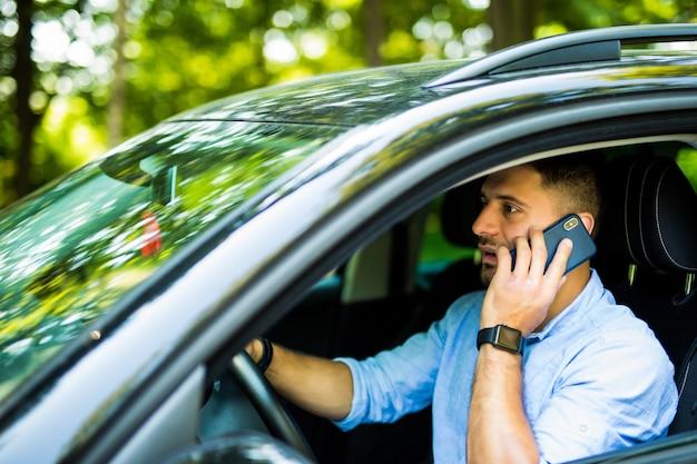 Portret van de jonge knappe man auto rijden en spreken op mobiele telefoon