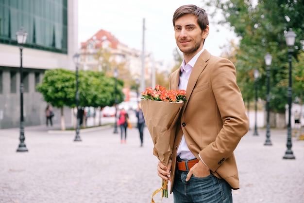 Portret van de jonge knappe man die lacht houden van een bos rozen