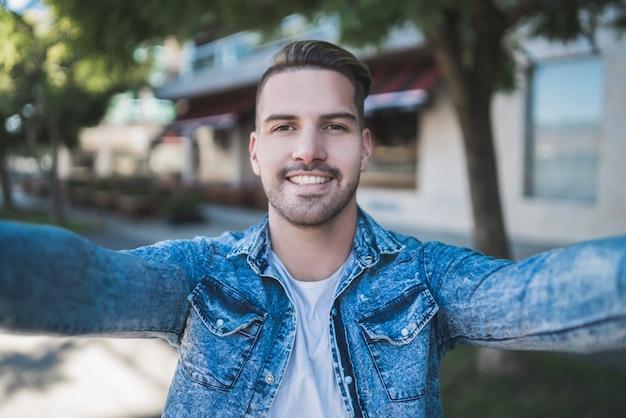 Portret van de jonge knappe man die vrijetijdskleding draagt en een selfie buiten in de straat neemt