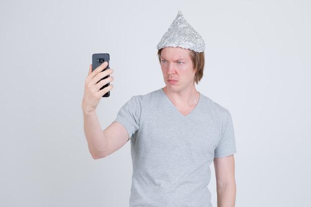 Portret van de jonge knappe man met aluminiumfolie hoed als concept van de complottheorie op wit