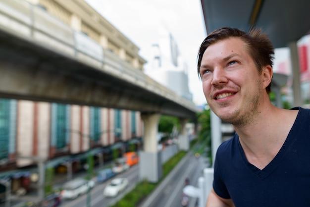 Portret van de jonge knappe man op sky treinstation in de stad buitenshuis