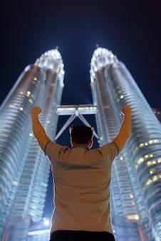 Portret van de jonge knappe man tegen lage hoekmening van de petronas twin towers 's nachts in kuala lumpur, maleisië
