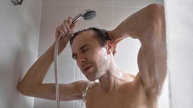 Portret van de jonge knappe man wast zichzelf met douchegel, schuimt hoofd met shampoo in de badkamer thuis close-up