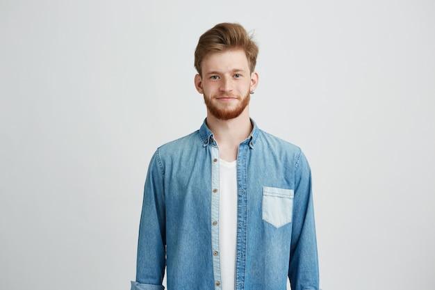 Portret van de jonge knappe mens in het overhemd van jean glimlachen die camera bekijken.