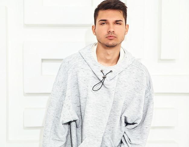 Portret van de jonge knappe modelmens gekleed in grijze toevallige hoodiekleren die dichtbij geweven witte muur stellen