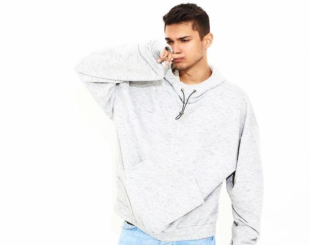 Portret van de jonge knappe modelmens gekleed in grijze toevallige hoodiekleren die op witte muur stellen. geïsoleerd