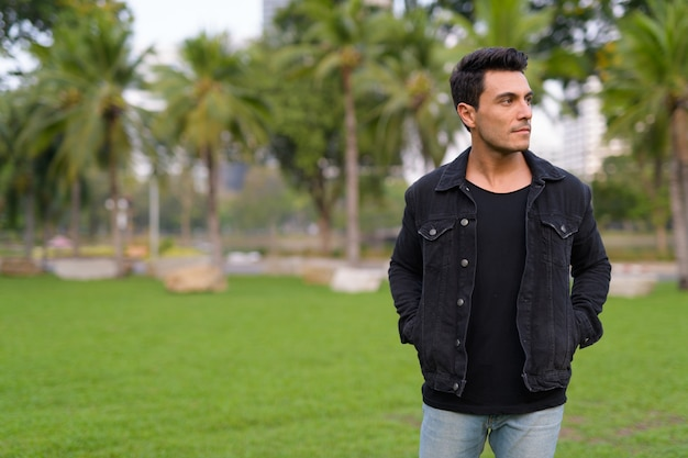 Portret van de jonge knappe spaanse man in het park buiten