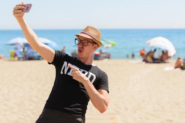 Portret van de jonge knappe toeristenmens als nerd op het strand in spanje