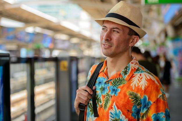 Portret van de jonge knappe toeristenmens bij skytrain-station in de stad