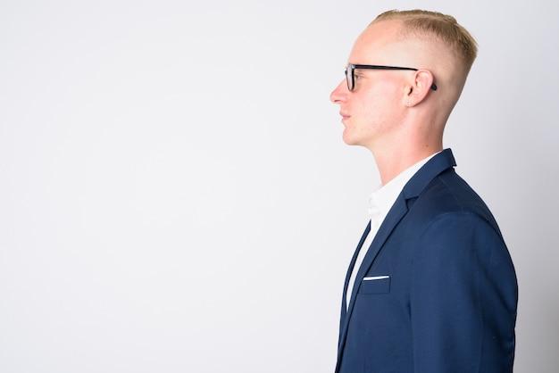 Portret van de jonge knappe zakenman met kort blond haar in pak en bril op wit